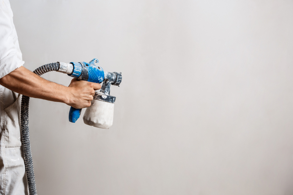 worker-painting-wall-with-spray-gun-in-white-color